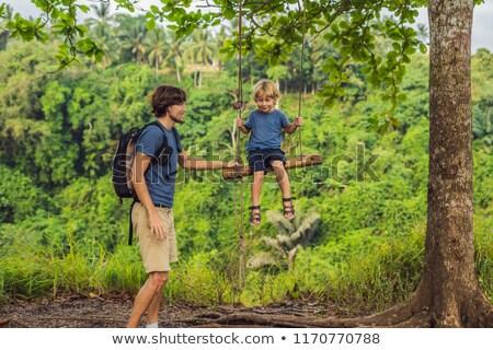Baba oğul salıncak yürümek bali ağaç Stok fotoğraf © galitskaya