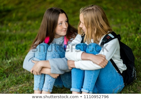 two cheerful young girls students sitting on a grass stock photo © deandrobot