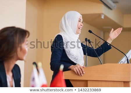 Happy young female speaker in hijab laughing while standing by tribune Stock photo © pressmaster