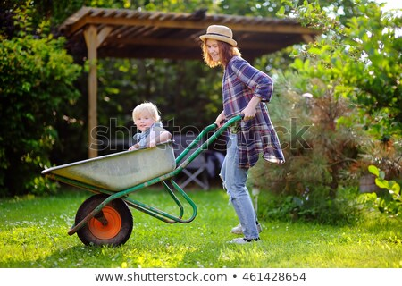 Boy And Girl Sitting In Wheelbarrow stock photo © monkey_business