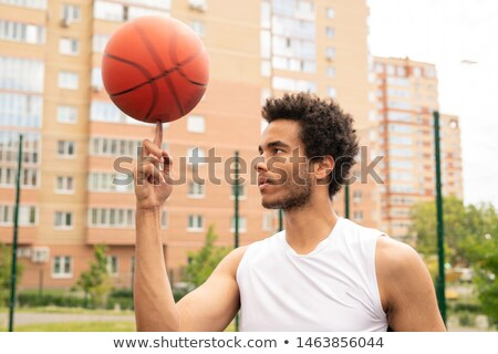 Young active professional basketball player holding rotating ball on forefinger Stock photo © pressmaster