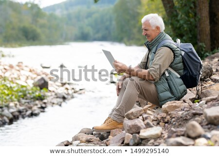 mature backpacker with touchpad using video chat to communicate with his wife stock photo © pressmaster