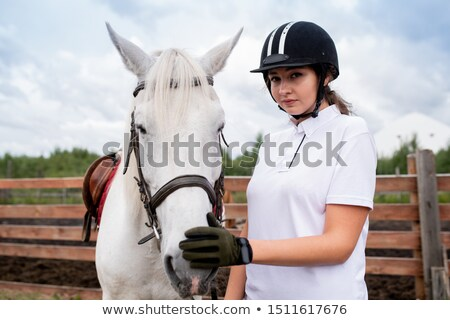 Pretty girl in equestrian helmet and gloves touching nose of white racehorse Stock photo © pressmaster