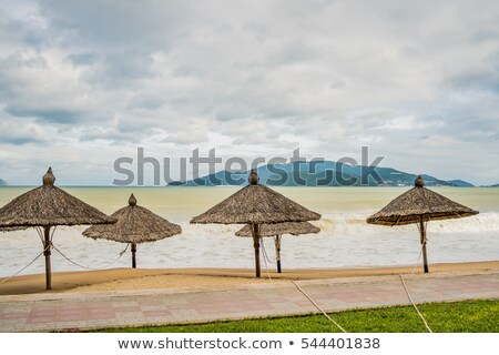 Beach in bad weather. Emptiness, high waves and parasols made of natural materials Stock photo © galitskaya
