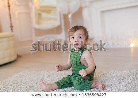 Boy 1 year sitting on the carpet in a bright room Stock photo © ElenaBatkova