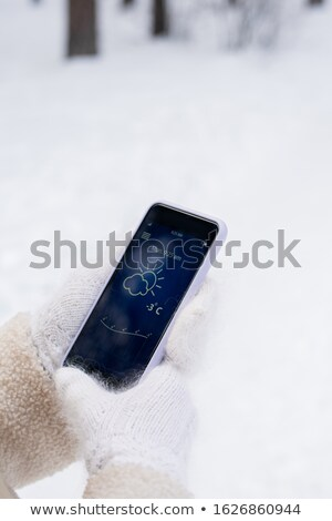 Hands of girl in mittens looking for temperature outside in smartphone Stock photo © pressmaster