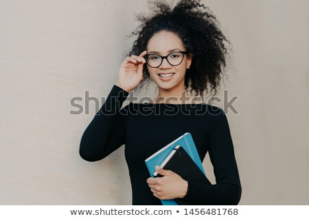 Portrait of cute frizzy young woman with gentle smile, keeps hand on rim of glasses, wears casual bl Stock photo © vkstudio