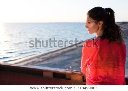 Pretty female feels enjoyment while stands against sea background, shows her perfect slim body, clos Stock photo © vkstudio