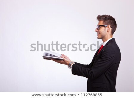 Stock photo: business man looking at something comming out of his book