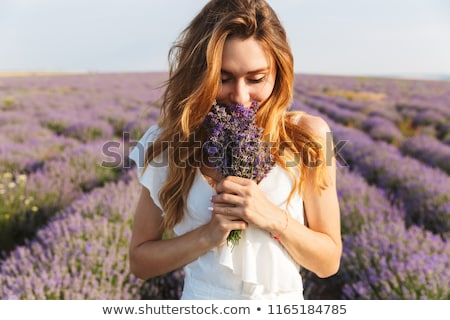 woman smelling bouquet of flowers stock photo © dolgachov