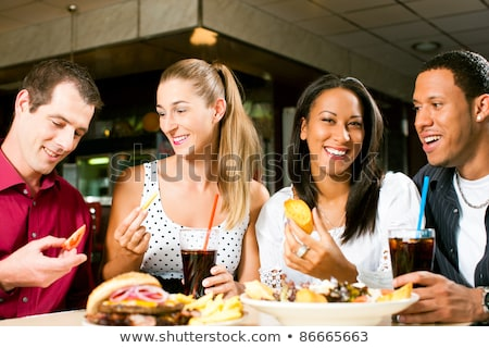 Friends or couple eating fast food with burger and fries  Stock photo © Kzenon