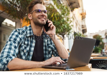 smiling young casual man with glasses sitting on the sidewalk Stock photo © feedough