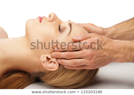 young caucasian woman lying down smiling and receiving head massage stock photo © ambro