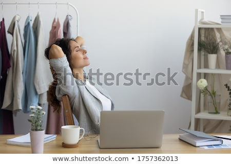 tired female tailor sitting at the table stock photo © deandrobot