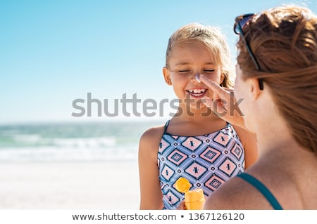 Stock photo: happy woman sunbathing and applying sunscreen