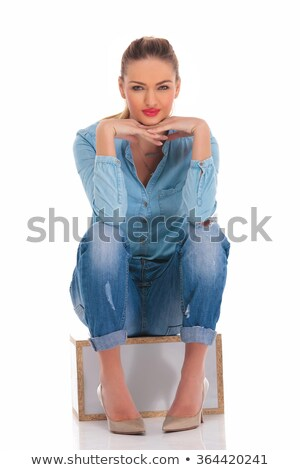 woman in denim pose seated with hands on knees touching face Stock photo © feedough