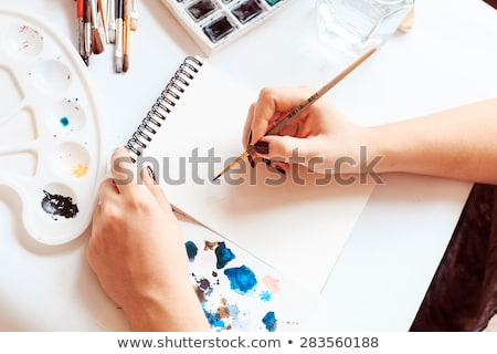 process of painting with watercolors a palette and brush in hand stock photo © marysan