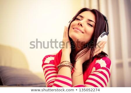 Fiatal mosolyog gyönyörű nő hallgat zene fülhallgató Stock fotó © deandrobot