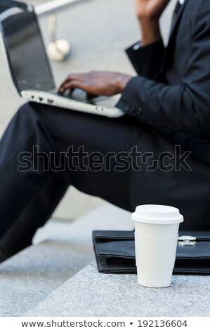 young man using laptop while sitting on the staircase outdoors stock photo © deandrobot