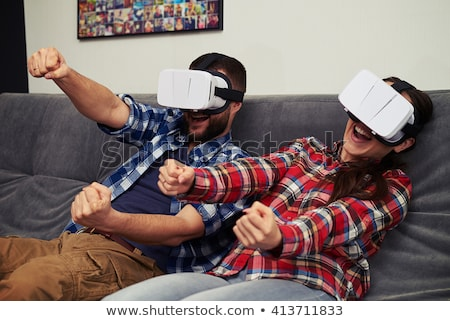 Young shocked bearded man wearing virtual reality device Stock photo © deandrobot