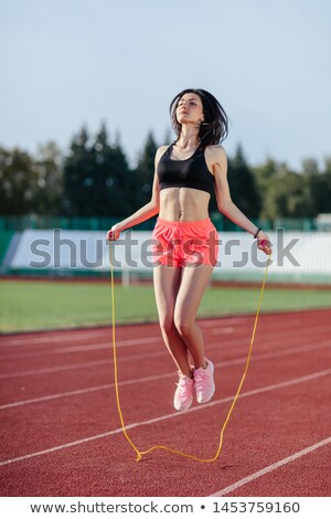Stock photo: Beautiful sports blonde the woman with a jump rope at stadium. S