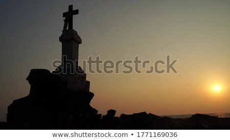 seacoast at sunset and a cross on a rock stock photo © all32