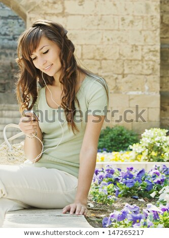 Women sitting on wall with mp3 player Stock photo © IS2