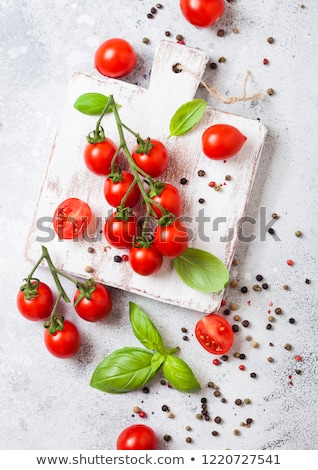 Organic Cherry Sugardrop Tomatoes on the Vine with basil in oilve wood plate and spoon with pepper o stock photo © DenisMArt
