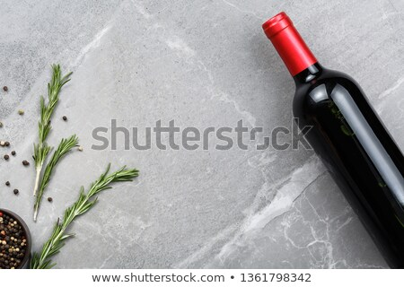 Elegant glass and bottle of red wine on stone kitchen table background. Top view. Space for text Stock photo © DenisMArt