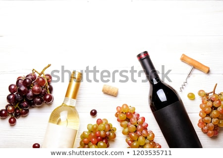 Red wine bottle and corkscrew on black matte background. Stock photo © dash