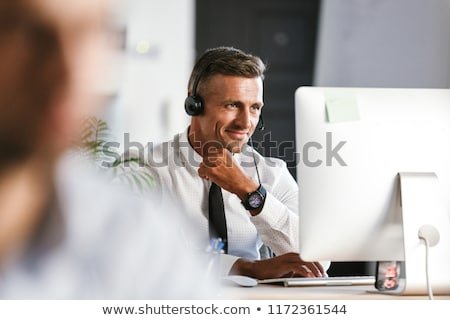 Photo stock: Photo Of Smiling Operator Man 30s Wearing Office Clothes And Hea