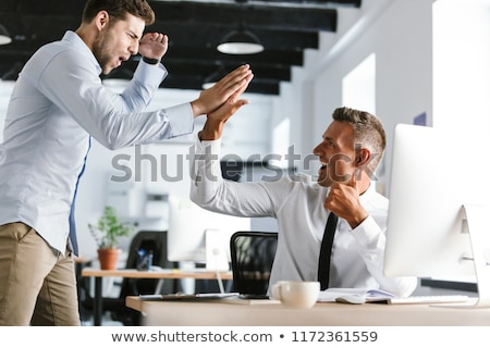 Photo of happy businessmen 30s in formal clothes giving high fiv Stock photo © deandrobot