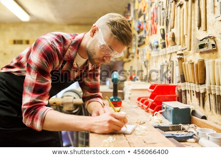 carpenter writing to notebook at workshop stock photo © dolgachov