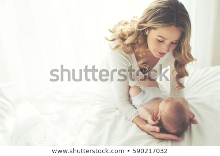 portrait of beautiful young parents and cute baby on bed stock photo © lopolo