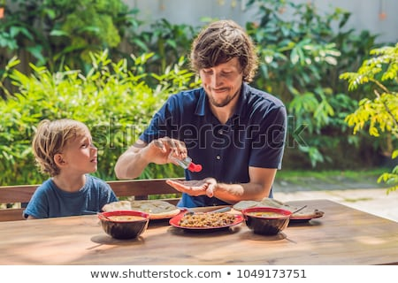 father and son using wash hand sanitizer gel before eating in a cafe with sunlight stock photo © galitskaya