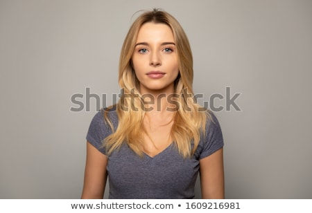 Close up of blonde young lady on grey studio background.  Stock photo © studiolucky