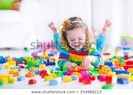 happy baby girl playing with toy blocks at home stock photo © dolgachov