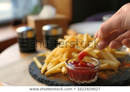 Woman hands on slate table with french fries Stock photo © lightkeeper