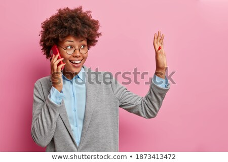 Positive curly haired businesswoman wears spectacles, formal wear, has bushy hairstyle, being in goo Stock photo © vkstudio