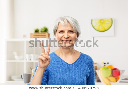 Mosolyog idős nő mutat béke konyha Stock fotó © dolgachov