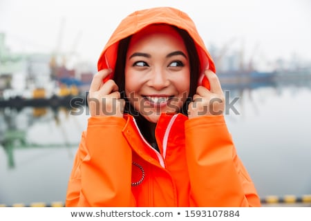 attractive young asian woman wearing raincoat walking outdoors stock photo © deandrobot