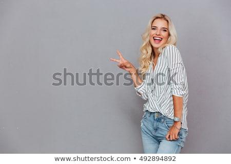 fiatal · mosolygó · nő · győzelem · kézmozdulat · portré · fehér - stock fotó © feedough