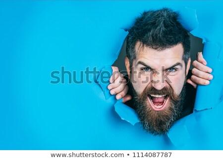 Joven mirando agujero papel rasgado hombre fondo Foto stock © photography33