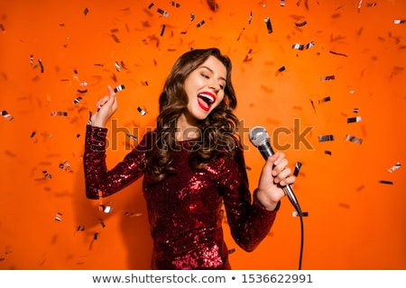 beautiful girl holding microphone and singing in a dress stock photo © feelphotoart