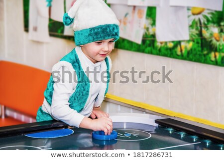 Cheerful little boy playing air hockey and having fun Stock photo © deandrobot