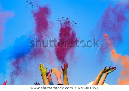 At the color Holi Festival, hands in the air, blue sky behind Stock photo © Nobilior