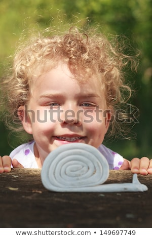 young pretty blond girl with curly blond hair and little lowers happy smiling on blue sky background stock photo © iordani