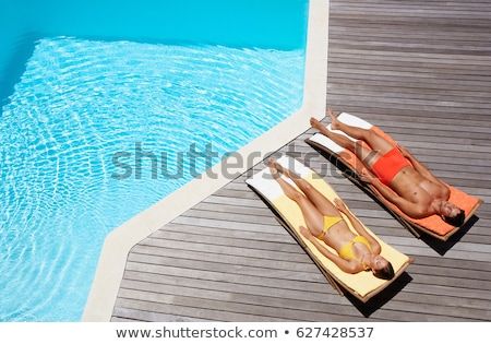 Woman relaxing on sun lounger by pool Stock photo © IS2