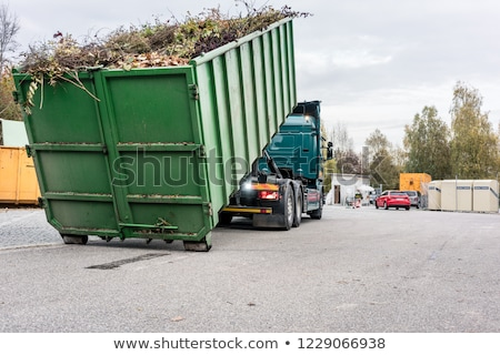 Truck loading container with waste green at recycling center Stock photo © Kzenon