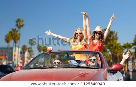 woman in convertible car waving hand over beach stock photo © dolgachov